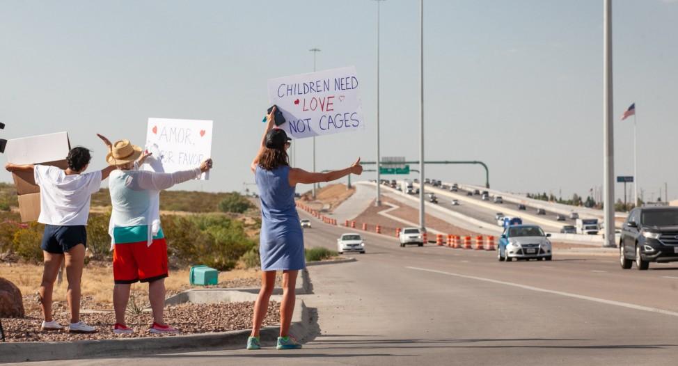 Anhaltender Protest: Drei Menschen demonstrieren mit Plakaten an der Autobahn gegen die menschenunwürdige Unterbringung von Migranten, vor allem Kindern, in der Grenzkontrollstelle in Clint bei El Paso, Texas.