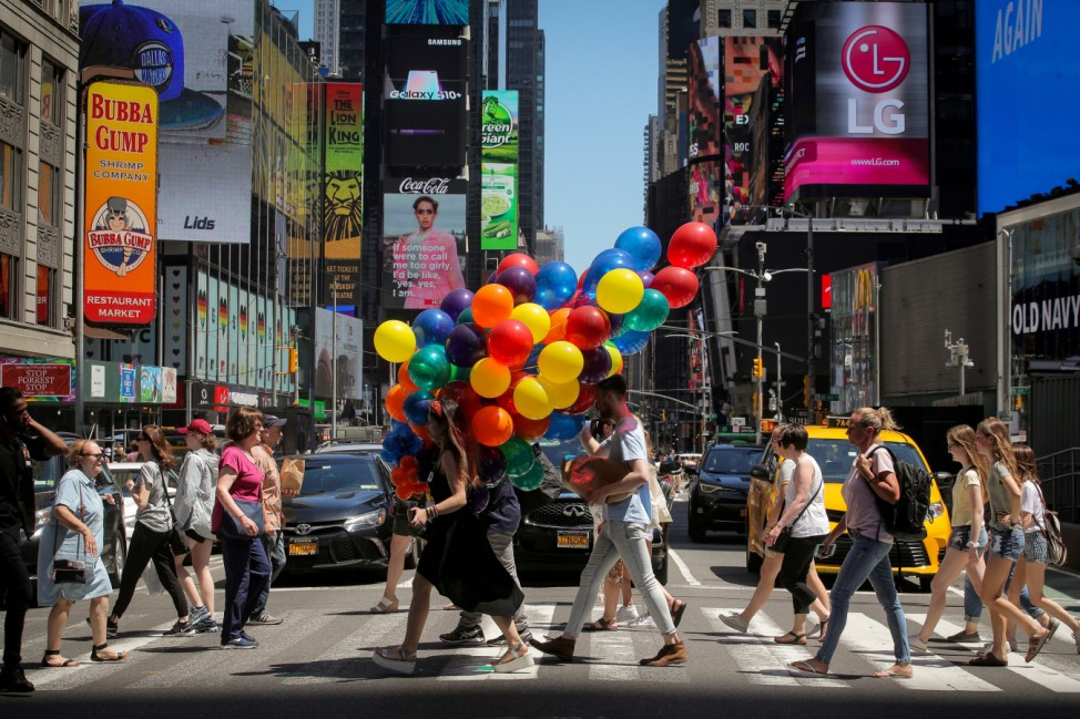 A woman carries a bunch of balloons through Times Square in New York