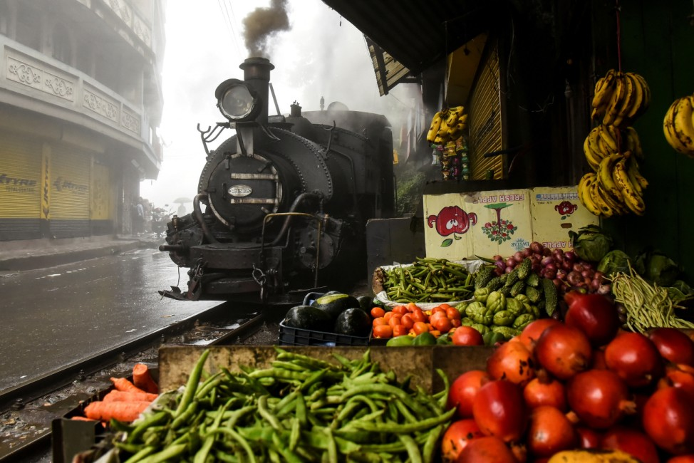 A Darjeeling Himalayan Railway steam train, which runs on a 2 foot gauge railway and is a UNESCO World Heritage Site, passes by a market in Ghum