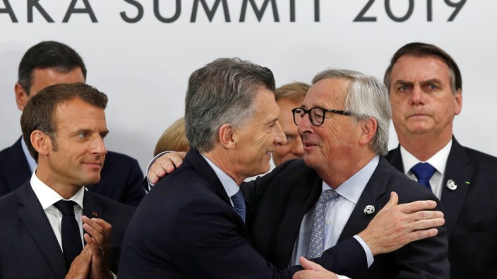 Argentina's President Mauricio Macri speaks to European Commission President Jean-Claude Juncker during a news conference at the G20 summit in Osaka