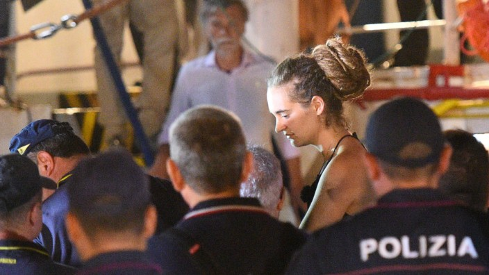 Carola Rackete, the 31-year-old Sea-Watch 3 captain, is escorted off the ship by police and taken away for questioning, in Lampedusa