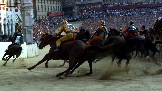 JOCKEYS TAKE THE SAN MARTINO TURN DURING PALIO OF SIENA HORSE RACE