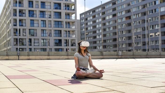junge Frau mit VR Brille sitzt im Schneidersitz in der Grossstadt Oesterreich Wien young woman wit