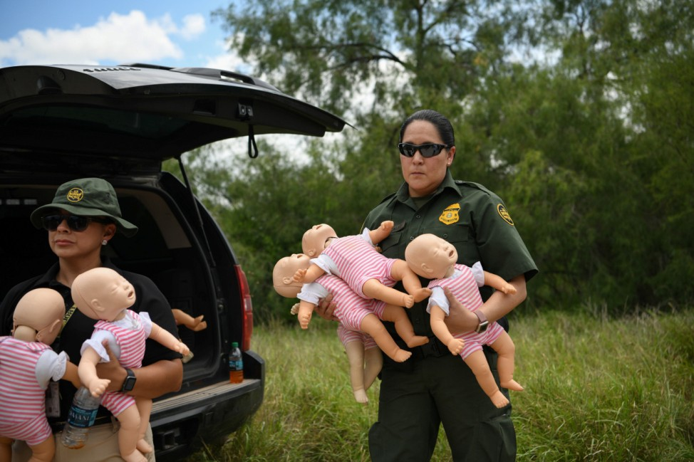 A U.S. Border Patrol agent holds infant dolls in preparation for a demonstration during a 'Border Safety Initiative' media event at the U.S.-Mexico border in Mission