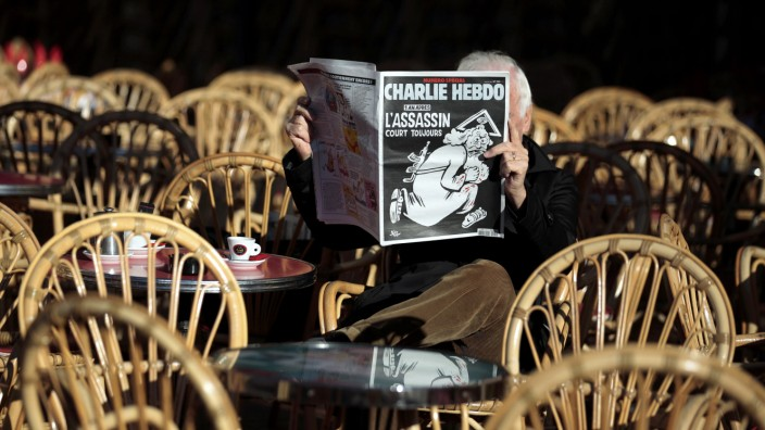A man reads the latest edition of French weekly newspaper Charlie Hebdo with the title 'One year on, The assassin still on the run' on a cafe terrasse in Nice
