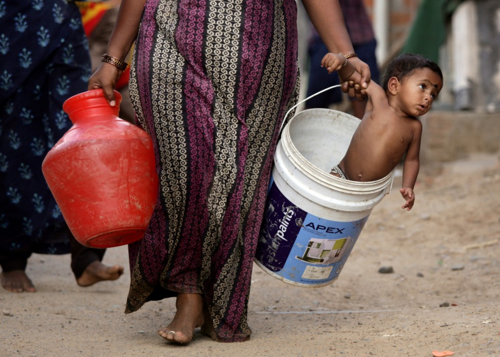 A woman carries her son in a bucket after collecting water from a municipal water tanker on the outskirts of Chennai