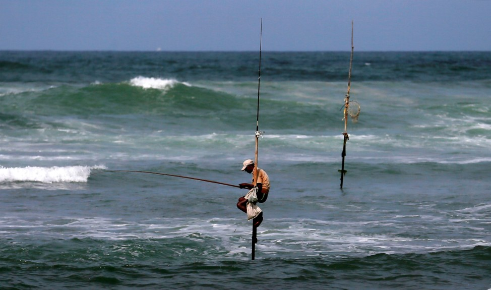 A fisherman waits to catch fish as he sits atop a stilt in the sea in Koggala