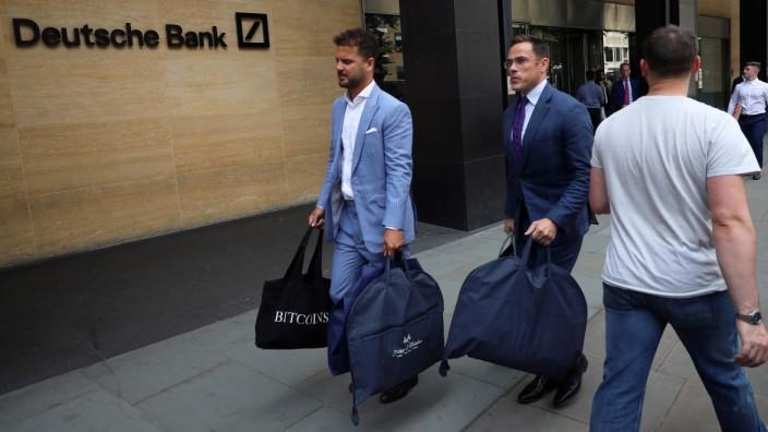 People carry bags outside a Deutsche Bank office in London