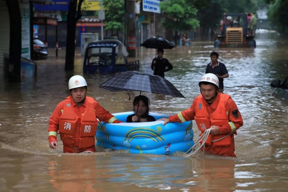 Planschboot: Helfer evakuieren eine Frau über eine überflutete Straße nach starken Regenfällen im chinesischen Pingxiang.