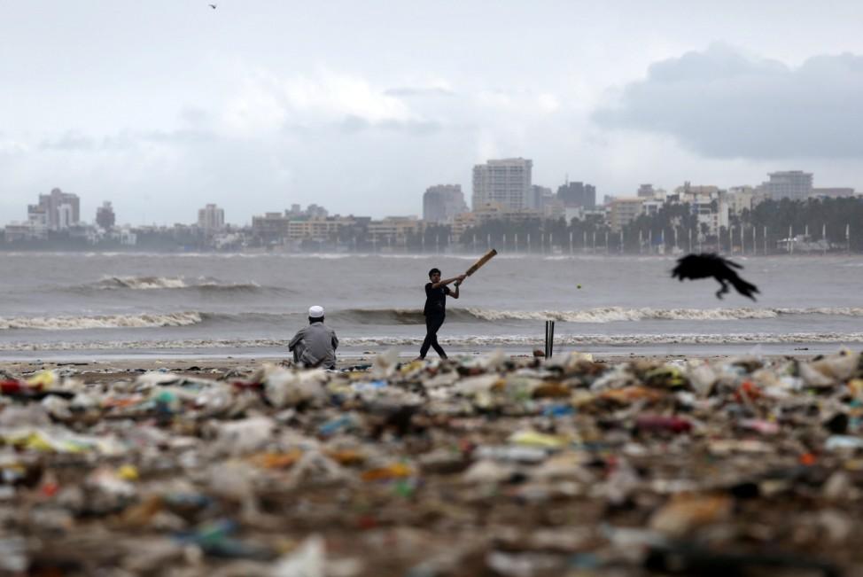 Verschmutztes Spielfeld: Ein Junge spielt Kricket an einem mit Plastikmüll übersäten Strand in Mumbai in Indien.