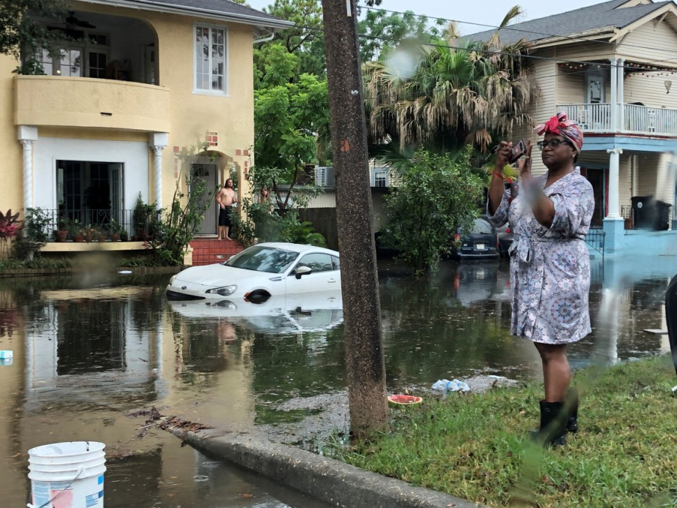 A pedestrian stands in flooded street in New Orleans