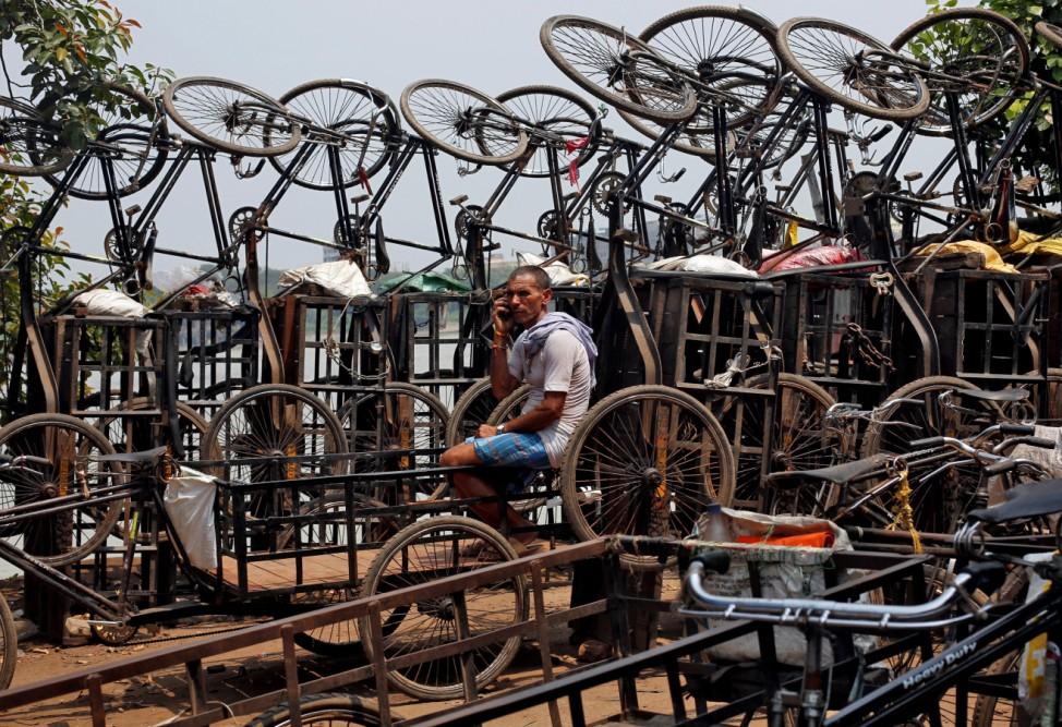 A man speaks on his mobile phone among parked trishaws in Kolkata