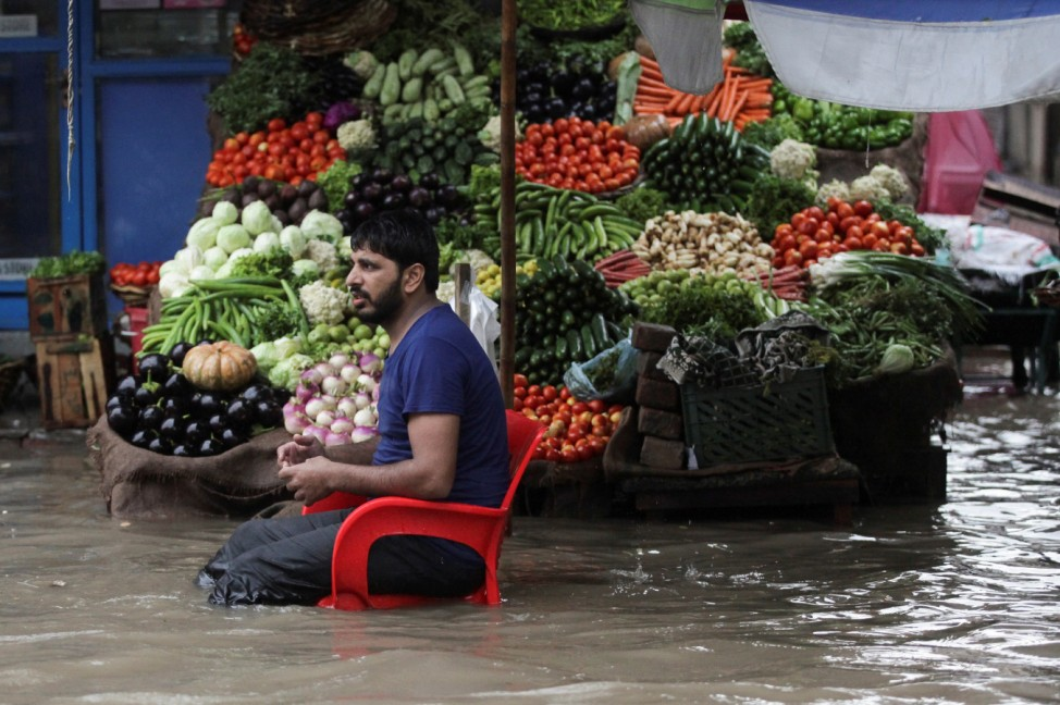 A vendor waits for customers as he sells vegetables amid floodwater, after the rain in Lahore
