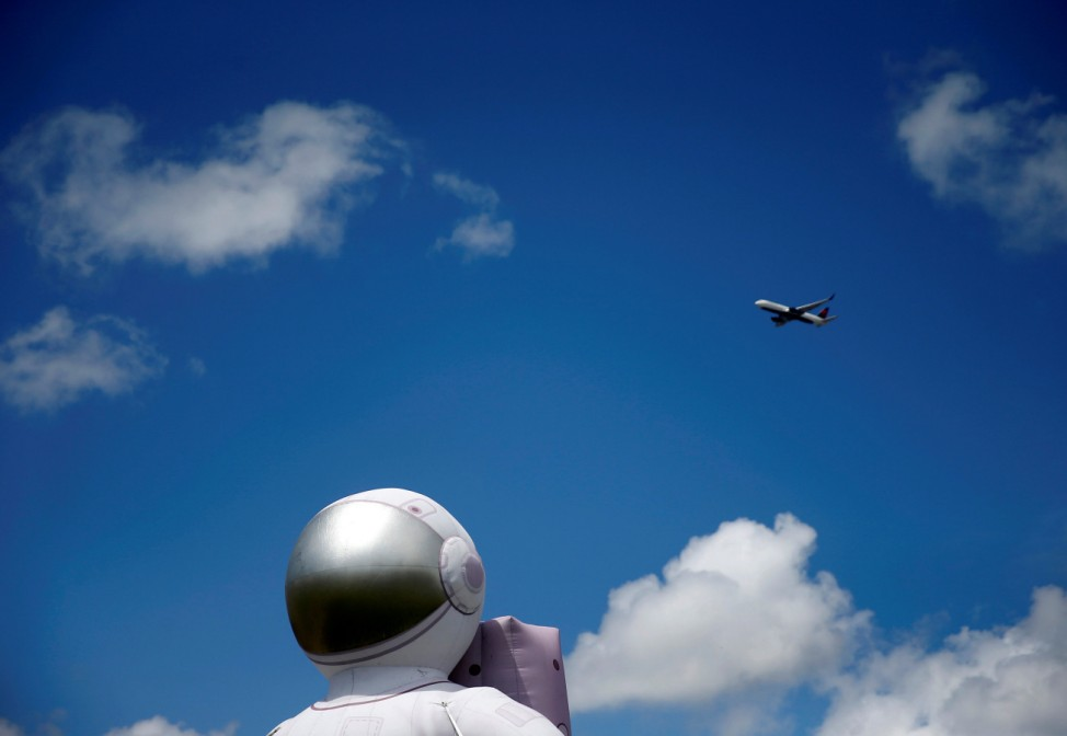 A plane passes by a large inflated astronaut outside the Museum of Flight on the anniversary of the Apollo 11 mission launch in Seattle