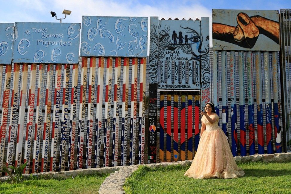 A girl poses in her quinceanera dress near the border fence between Mexico and U.S. in Tijuana