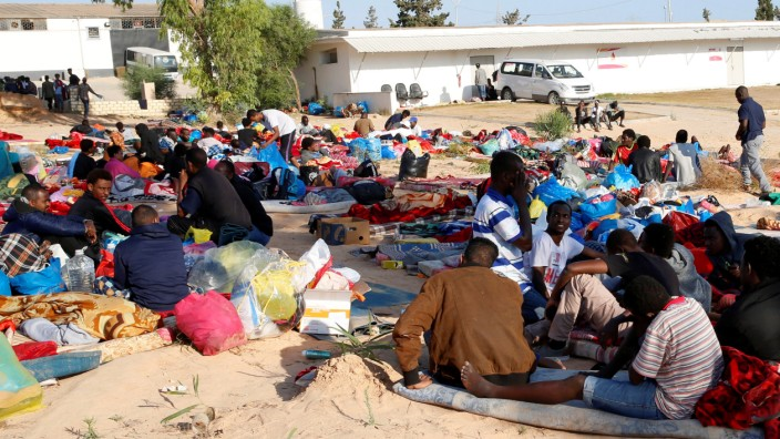 Migrants are seen with their belongings at the yard of a detention centre for mainly African migrants, hit by an airstrike, in the Tajoura suburb of Tripoli