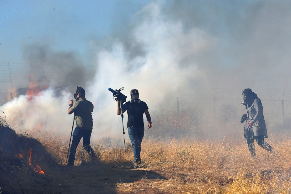 Journalists react to tear gas fired by Israeli forces during a protest against Israeli plans to demolish Palestinian homes, in the Palestinian village of Sur Baher in the Israeli-occupied West Bank
