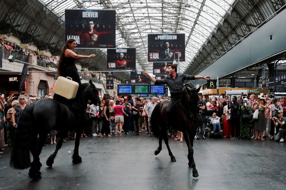 Artists Camille Galle and Emmanuel Bez aka Manolo of the Theatre du Centaure perform with horses at the Gare de l'Est train station in Paris