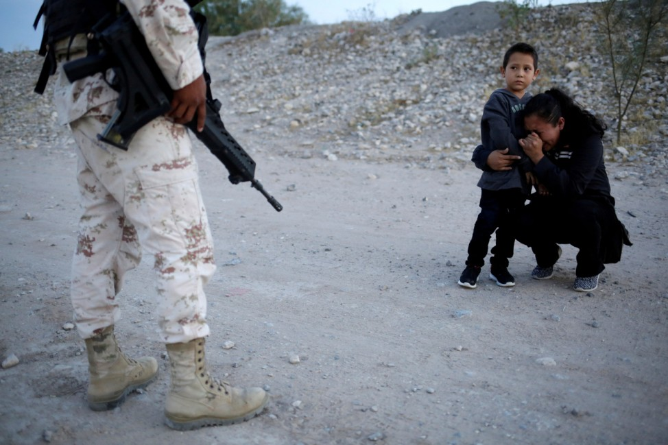 Guatemalan migrant Lety Perez embraces her son Anthony while praying to ask a member of the Mexican National Guard to let them cross into the United States, as seen from Ciudad Juarez