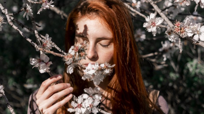Redheaded woman smelling tree blossoms model released Symbolfoto PUBLICATIONxINxGERxSUIxAUTxHUNxONLY