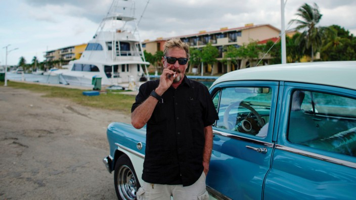 John McAfee smokes a cigarette before taking a taxi at the Marina Hemingway in Havana