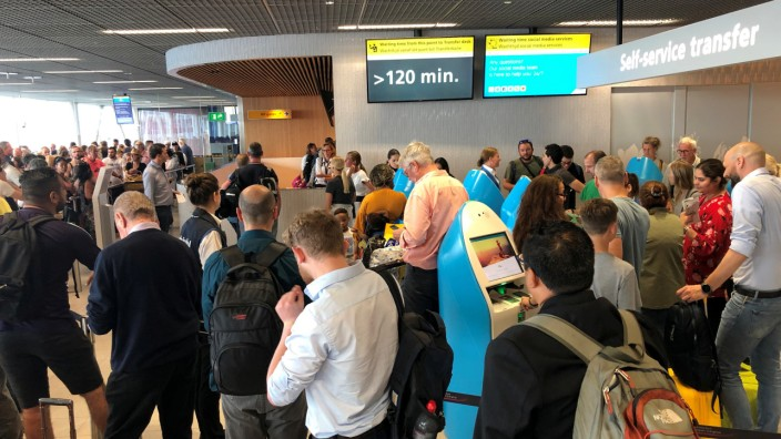 Passengers and staff wait at Amsterdam Schiphol airport