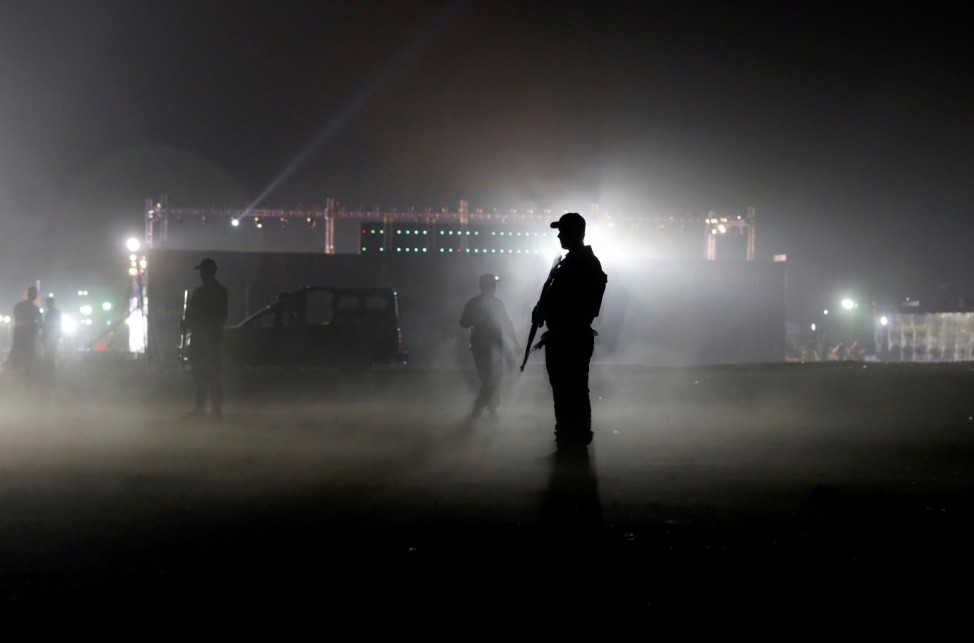A police officer is seen silhouetted against the flood lights at the venue during a countrywide protest called 'Black Day' against the government of prime minister Imran Khan, in Karachi