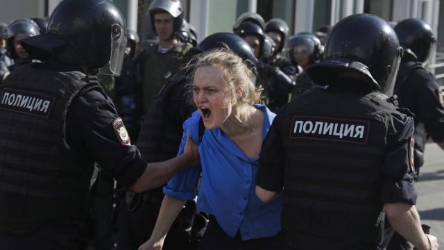 Eine junge Demonstrantin wird in Moskau von Polizisten abgeführt.