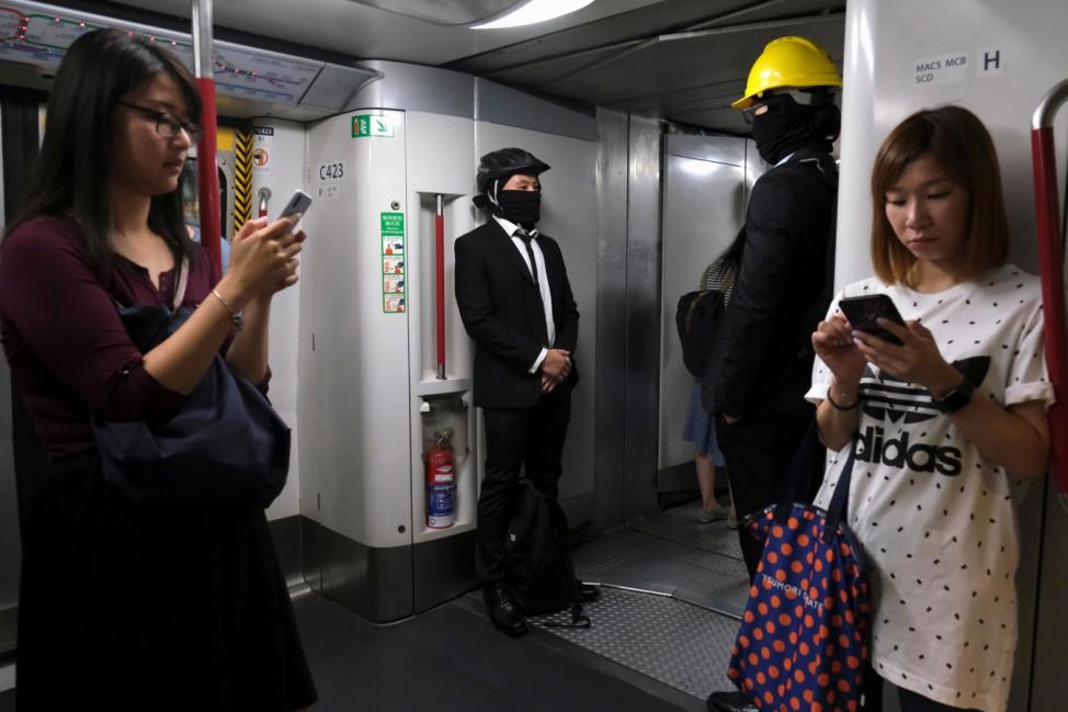 Anti-extradition bill demonstrators wearing helmets are seen inside a Mass Transit Railway (MTR) train in Hong Kong