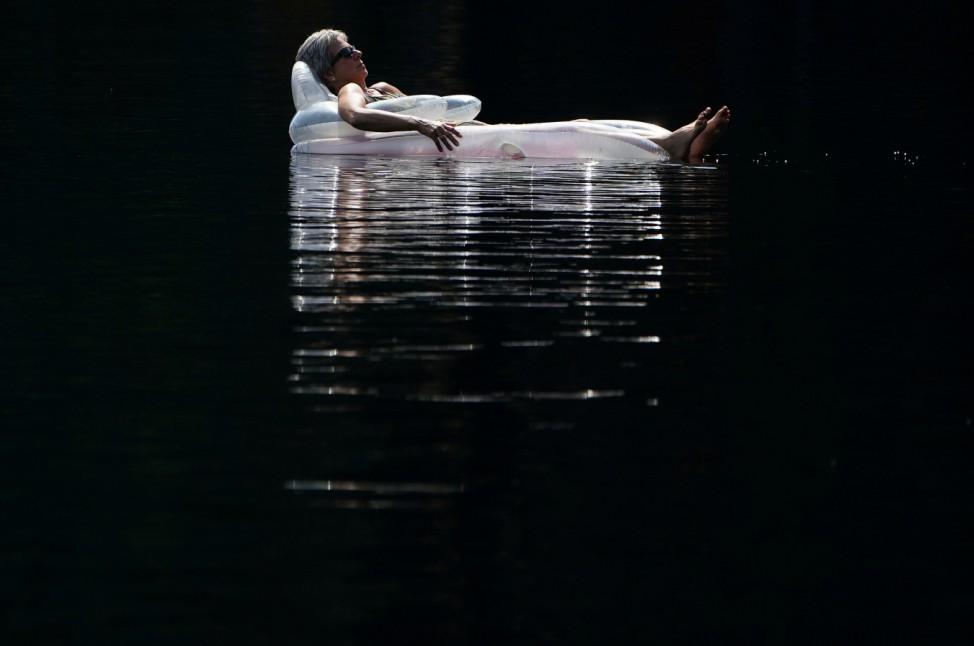 A woman floats on an air mattress in Mazinaw Lake at Bon Echo park in Cloyne