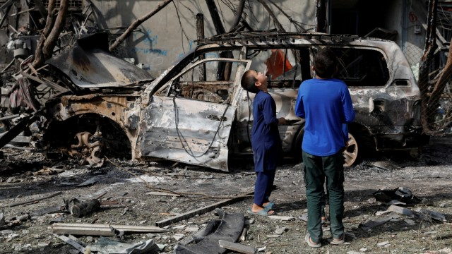 Afghan boys look the site of Sunday's attack in Kabul, Afghanistan