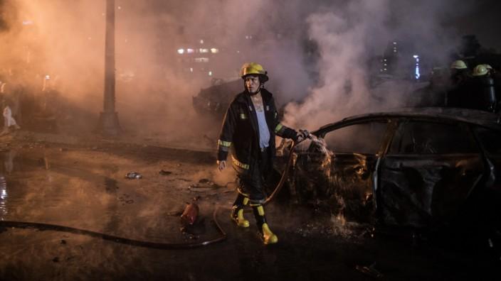 Feuerwehrmann löscht ein ausgebranntes Auto