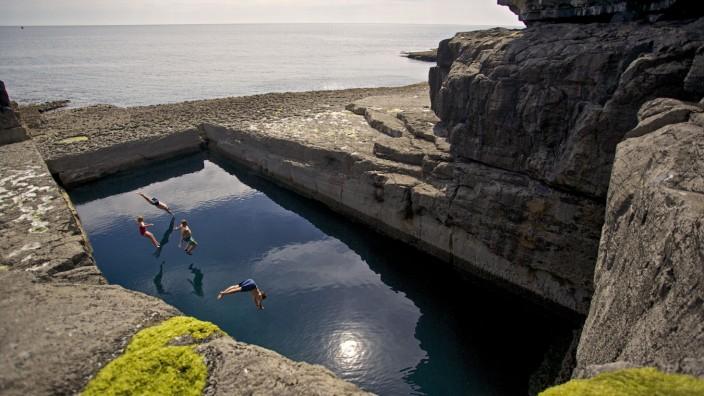 Schwimmer springen in ein natürliches Badebecken in Irland am Atlantik.