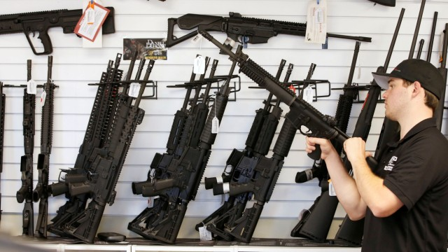 Salesman Ryan Martinez clears the chamber of an AR-15 at the 'Ready Gunner' gun store In Provo