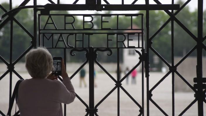"""Podiumsdiskussion in Dachau: Eine Besucherin der KZ-Gedenkstätte fotografiert das Tor mit dem zynischen Spruch """"Arbeit macht frei""""."""