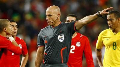 Fußball: Confed-Cup: Der britische Schiedsrichter Howard Webb wehrt sich nach seiner Elfmeterentscheidung gegen die wütenden Ägypter.