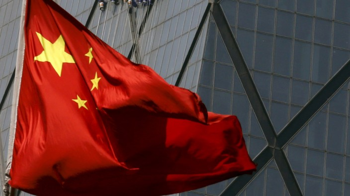 File photo of workers cleaning windows of a building behind China's national flag at a commercial district in Beijing
