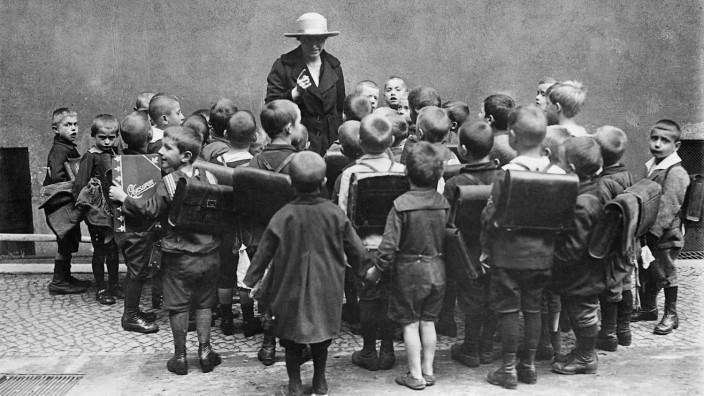 Eine Lehrerin ermahnt ihre Schüler, 1923
