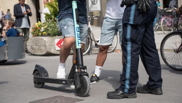 Bei einer Schwerpunktkontrolle kontrolliert ein Polizist am Odeonsplatz einen E-Scooter-Fahrer.