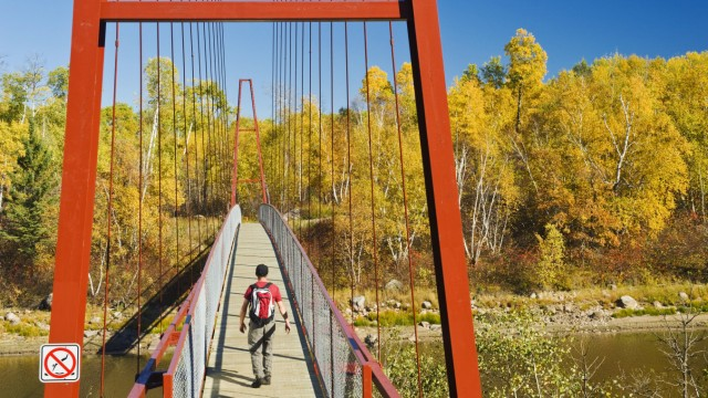 Hiker crosses a bridge over the Whiteshell River along the Trans Canada Trail Whiteshell Provincial