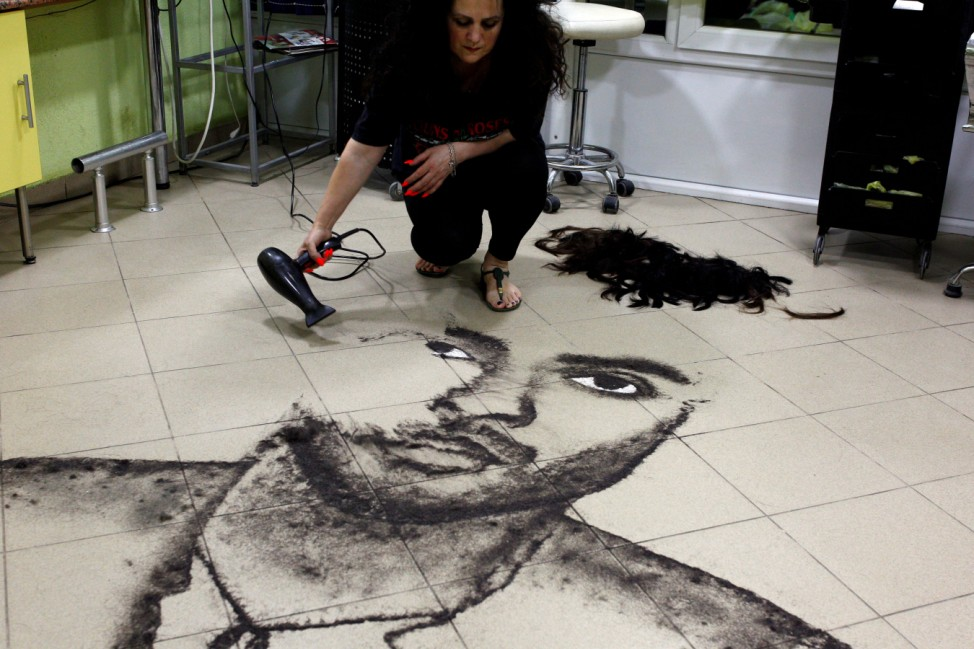 Hairdresser Svetlana Grozdanovska creates a celebrity's portrait on the floor of her salon using her clients' cut hair, in Krivogastani