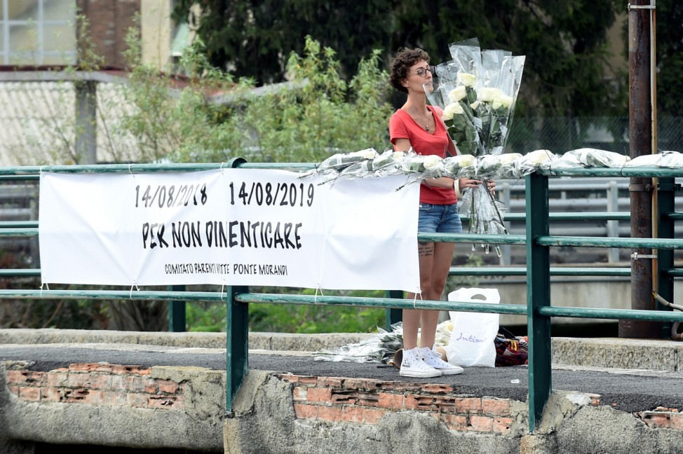 A woman pays tribute with flowers to bridge collapse victims, a day ahead of the first anniversary of Morandi bridge collapse in which 43 people died, in Genoa
