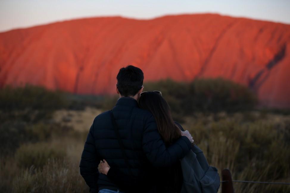 Sehnsuchtsort: Ein Paar umarmt sich vor der romantischen Kulisse des Uluru in Australien. Der Berg darf aus Respekt vor den Aborigines ab Ende Oktober von Touristen nicht mehr bestiegen werden.