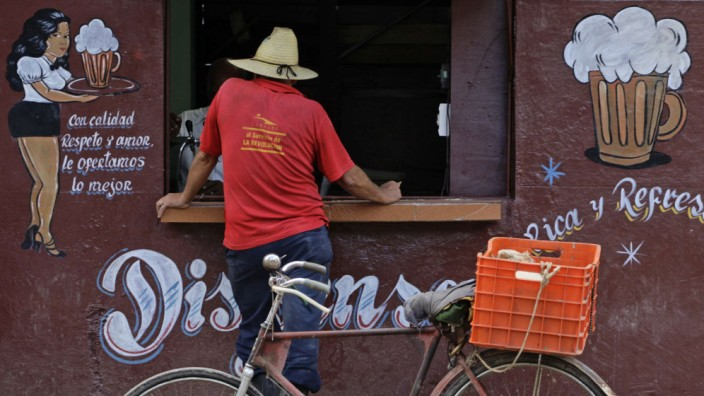 A farmer buys a beer at a stall on the outskirts of Havana