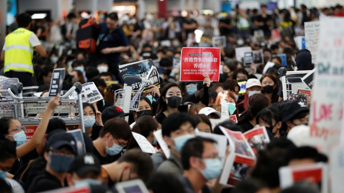 Anti-government protesters sit on the floor in front of security gates during a demonstration at Hong Kong Airport