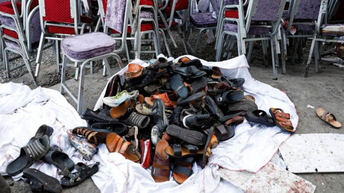 The shoes of victims are seen outside a damaged wedding hall after a blast in Kabul, Afghanistan