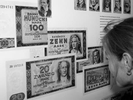 Foto: dpa, eine Besucherin einer Ausstellung der Bundesdruckerei betrachet alte DDR-Banknoten, Juni 1998