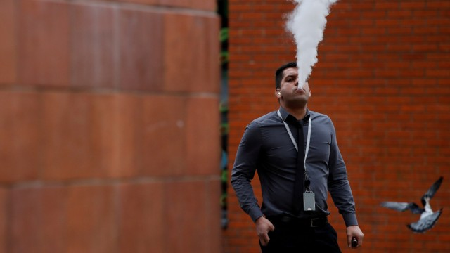 FILE PHOTO: A man vapes outside an office block in Manchester, Britain
