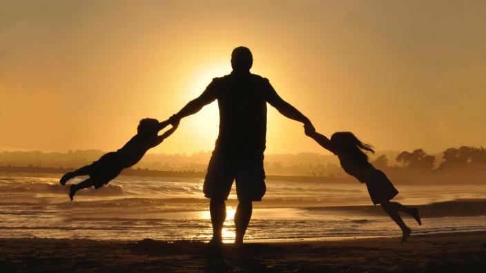 Ein Vater und zwei Kinder spielen beim Sonnenuntergang am Strand.