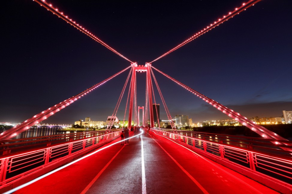 People walk along a pedestrian bridge illuminated on the occasion of the National Flag Day in Krasnoyarsk